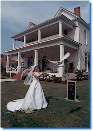 A woman in a wedding dress releasing a dove in front of a white house.